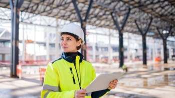 Woman with tablet standing on construction site and wearing safety gear