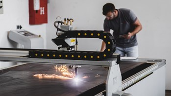 Male working with sheet metal machinery